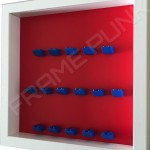 Blue Lego brick formation on red background side view
